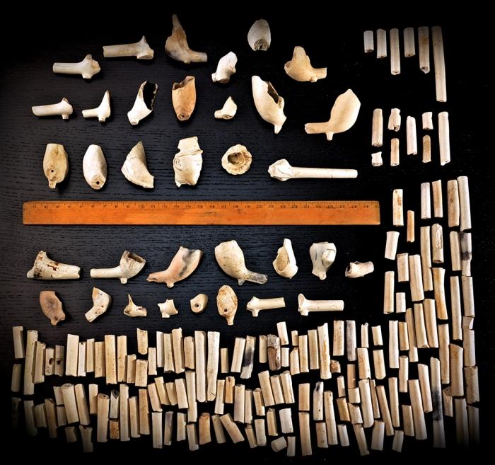 Suurolan pelloilta kerättyjä liitupiippuja. Ylhäällä on valmistajan merkein varustettuja pesän kappaleita, keskellä sellaisia pesän paloja, joista nämä merkinnät puuttuvat tai eivät ole säilyneet, sekä yhteensä 153 piipun varren katkelmaa.